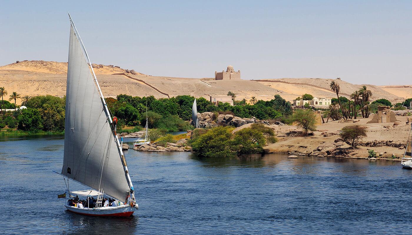 Assouan, felouques sur le Nil et mausolee de l'Agha Khan sur la rive ouest