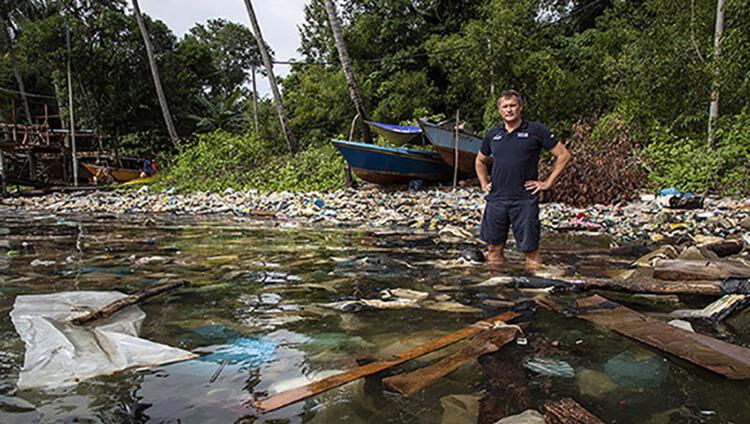 Marco Simeoni devant l'Océan à Bornéo jonché de déchets plastiques (c) Peter Charaf