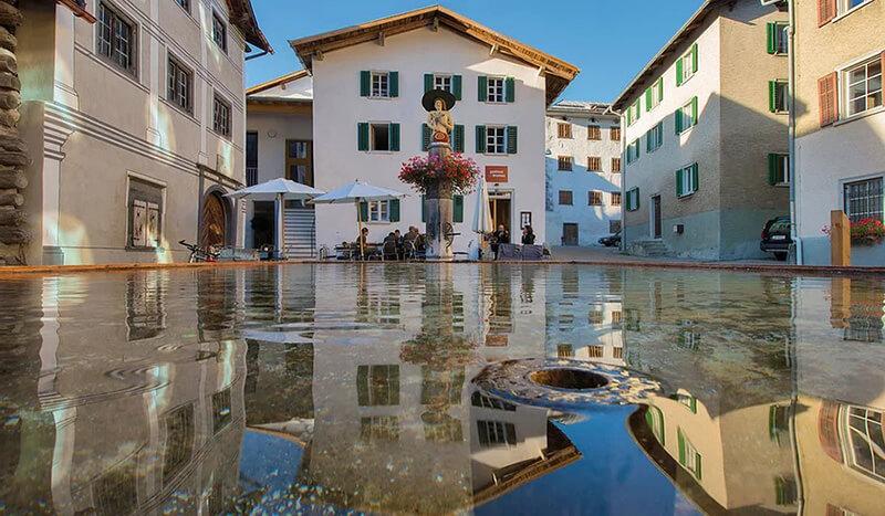 Hôtel Gasthaus am Brunnen une belle piscine et une statue fleurie pour accueillir les hôtes (c) Grisons Tourisme
