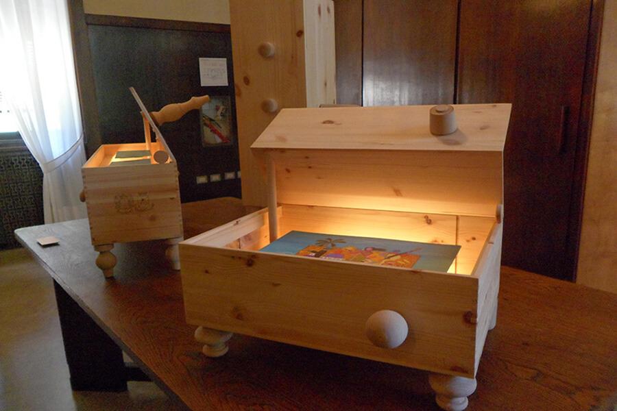 Un présentoir inspiré d'une caisse à vin accueillant une oeuvre de S. Vitale