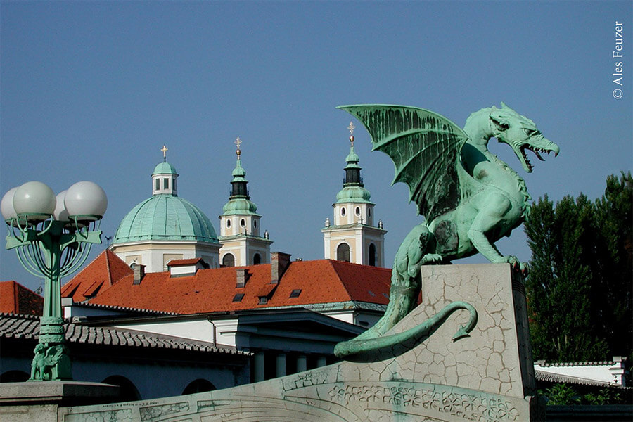 Ljubljana Le pont des Dragons et au loin la Cathédrale St Nicolas avec son dôme vert et ses tours jumelles