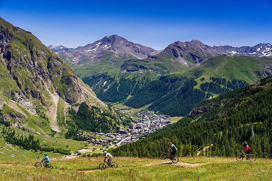 A vélo l'été sur une piste surplombant le village de Val d'Isère en contrebas (c) - Office du Tourisme Val d'Isere